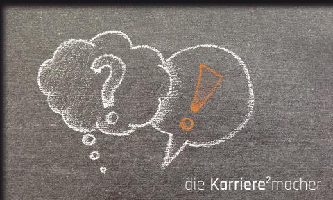 Thema: Unterschied zwischen Coaching und Mentoring; Kreidezeichnung auf Schiefertafel: Sprechblase mit einem Fragezeichen und Sprechblase mit einem Ausrufezeichen