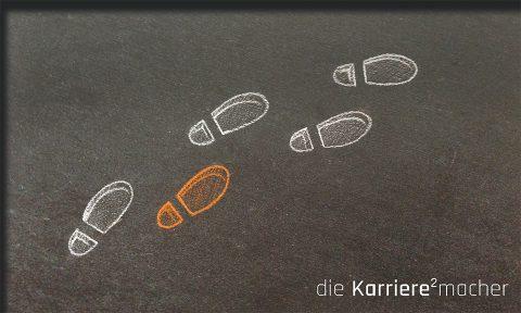 Kreidezeichnung auf Schiefertafel: Umrisse von Schuhabdrücken