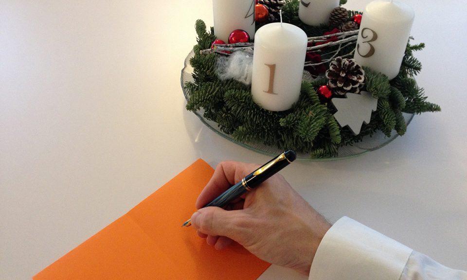 Foto: Adventskranz und schreibende Hand